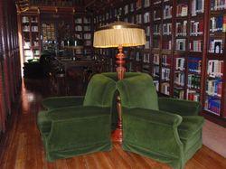 Tres butaques entapissades de verd col·locades al voltant d'un llum de peu de la zona de lectura