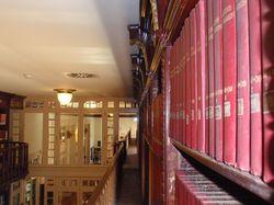 Imatge de la Sala de Lectura de la Biblioteca presa des de la galeria superior amb publicacions periòdiques antigues en primer terme
