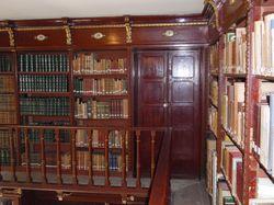 Porta d'entrada a la galeria superior de la Sala de Lectura emmarcada per la pròpia prestatgeria plena de llibres